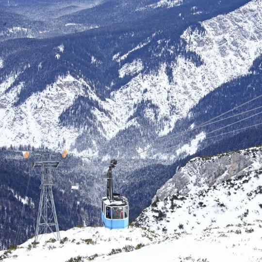 Fahren Sie mit der Gondel auf die Alpspitze