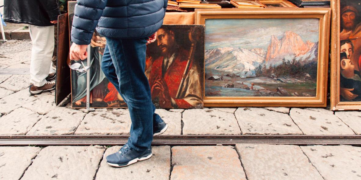 A man strolls by a stall selling oil paintings