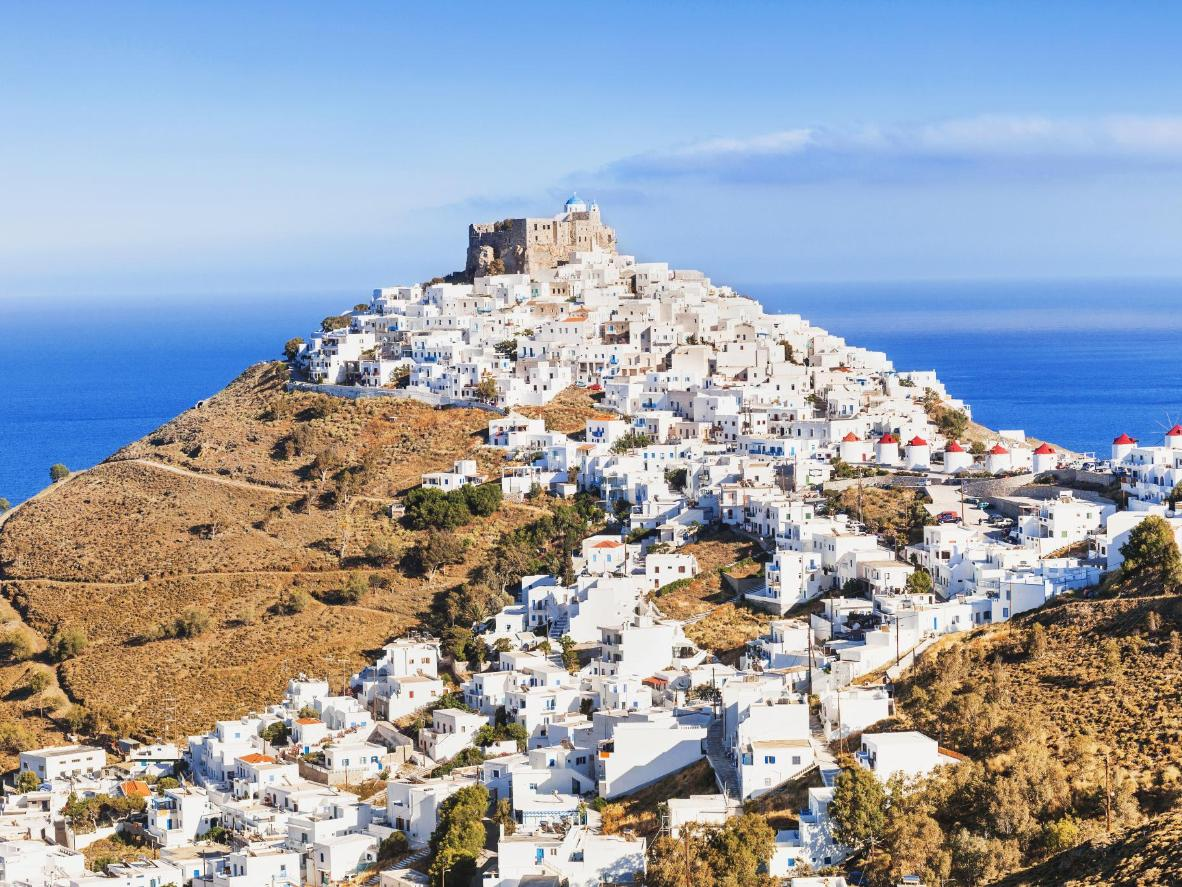 Bright, white-washed villages contrast against the blue of the Aegean Sea