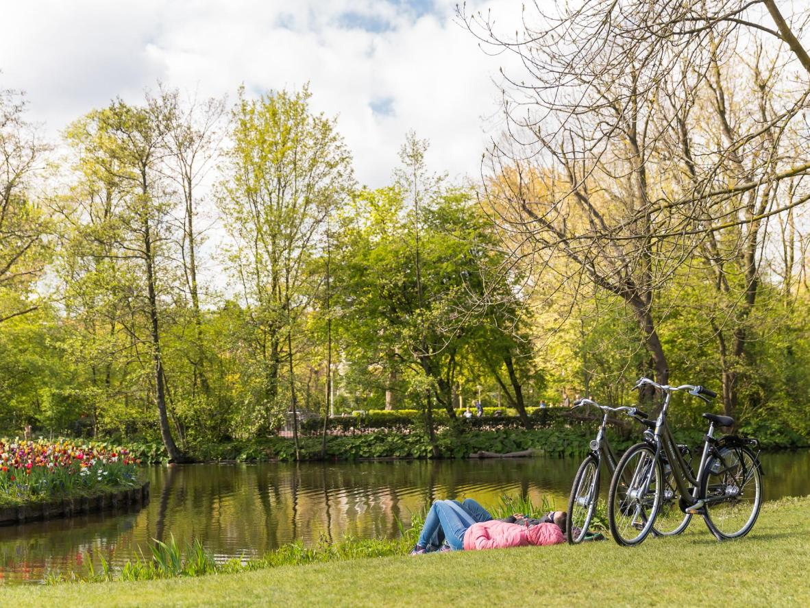 A couple relax by the water in Vondelpark