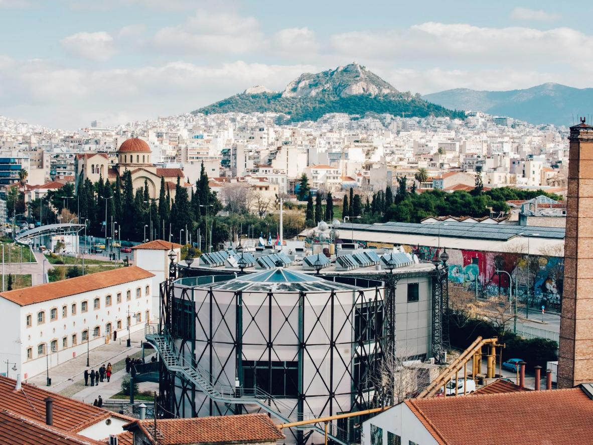The building is a modern spectacle amidst the ancient sprawl of Athens