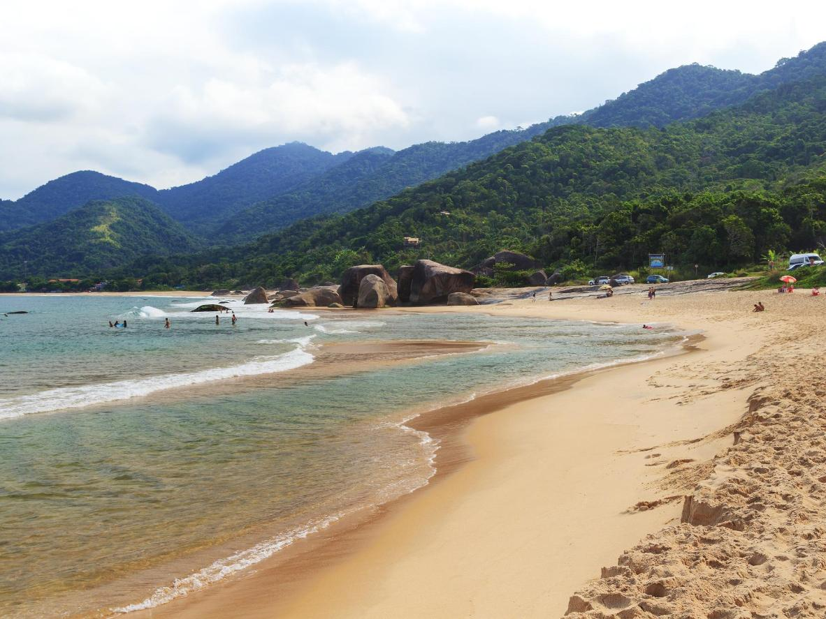 The sandy shores of Praia do Cepilho, enveloped by rolling green hills