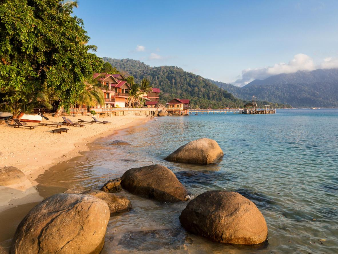 Tioman's jungle-covered hills rise up behind bungalows