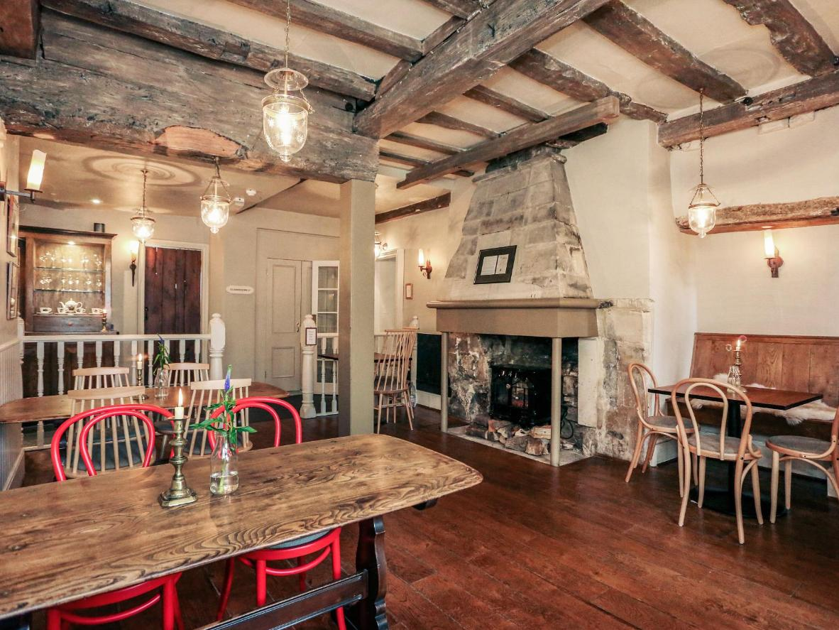A traditional log fire and beamed ceilings give the dining space a rustic feel