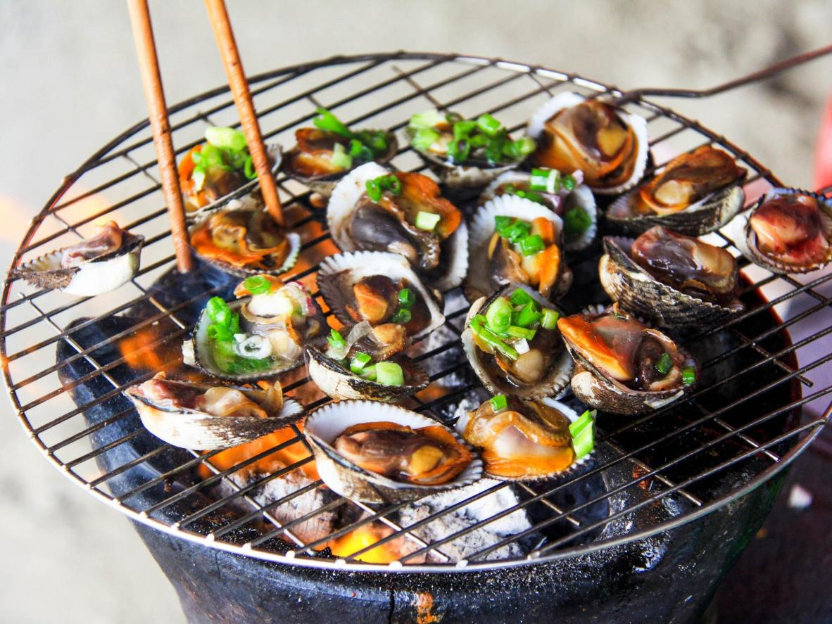 Fresh seafood is cooked on an open fire and topped with spring onions