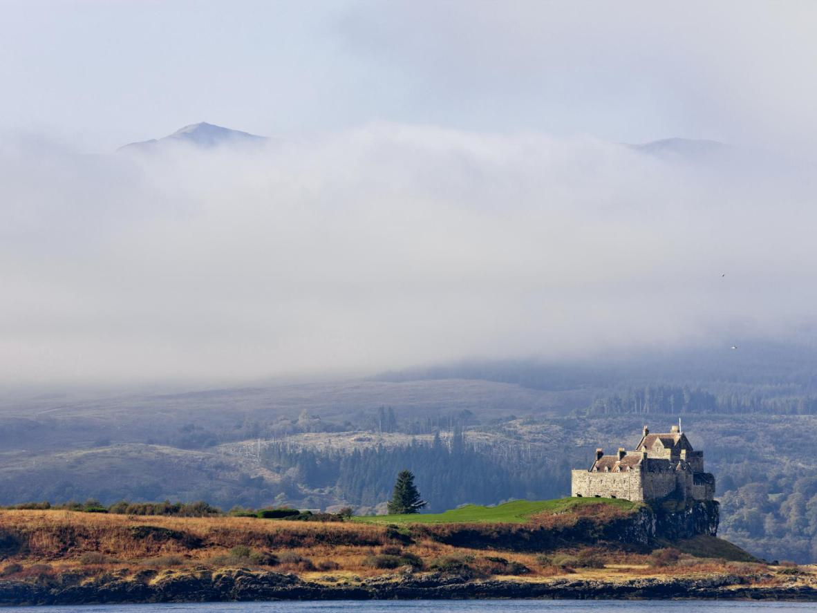 Duart Castle, the ancestral home of Clan MacLean, as the morning fog lifts from the mountains of Mull