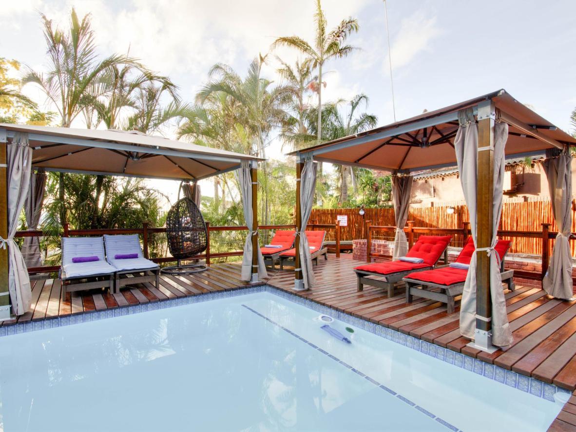 Palmeras y cabañas junto a la piscina hacen que este albergue se sienta como un resort de lujo.