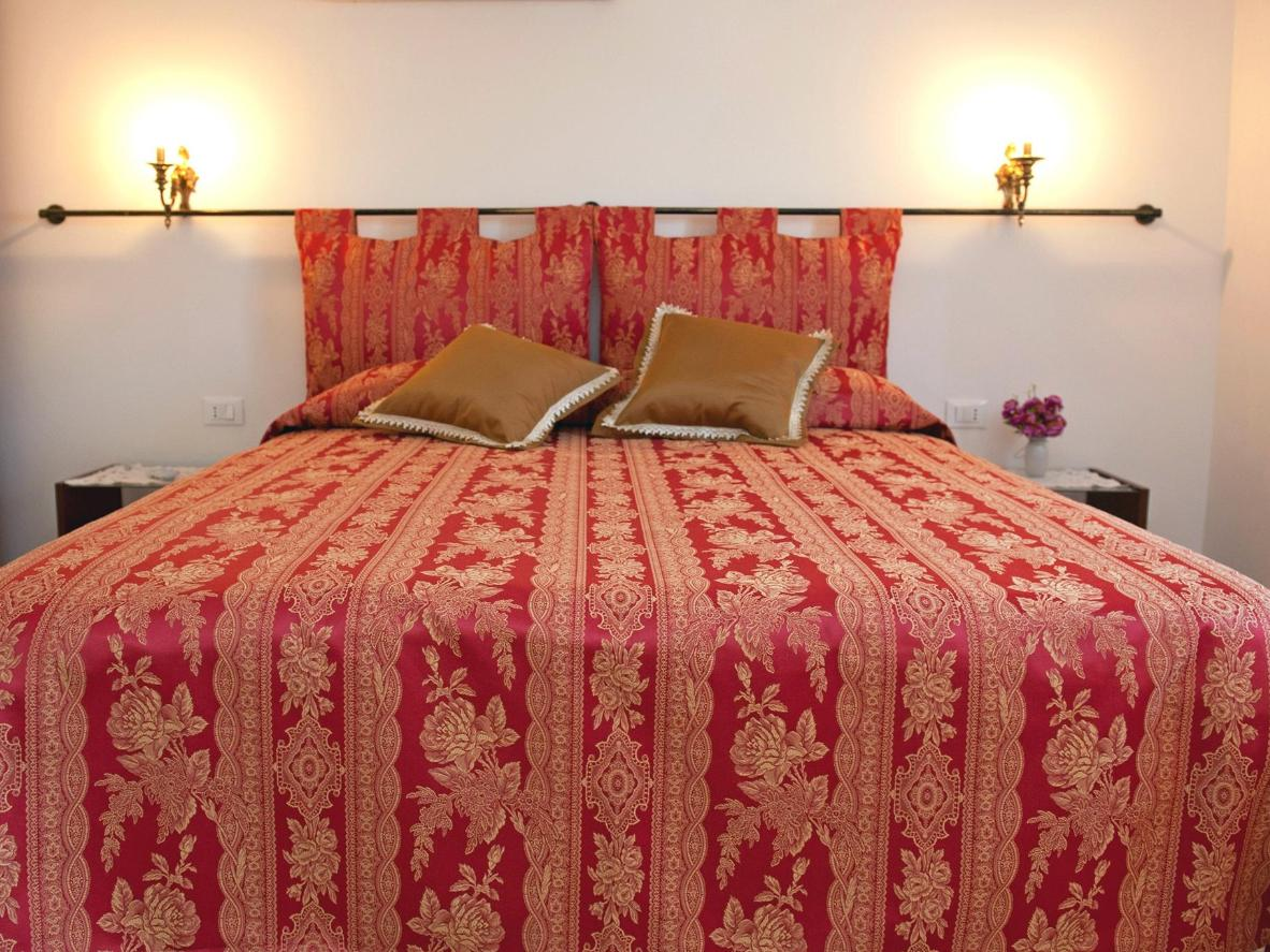 Bedrooms have brocade headboards and candle-style lights