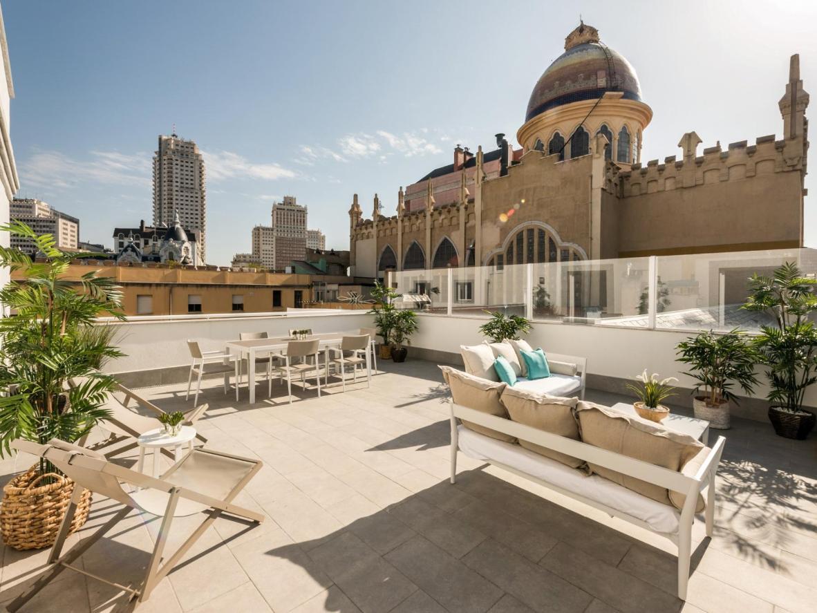 El apartamento de lujo tiene una gran terraza con una mesa de comedor y sala de estar