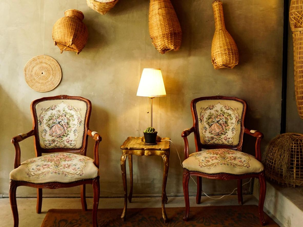 Vintage Louis XV armchairs and traditional Thai crafts
