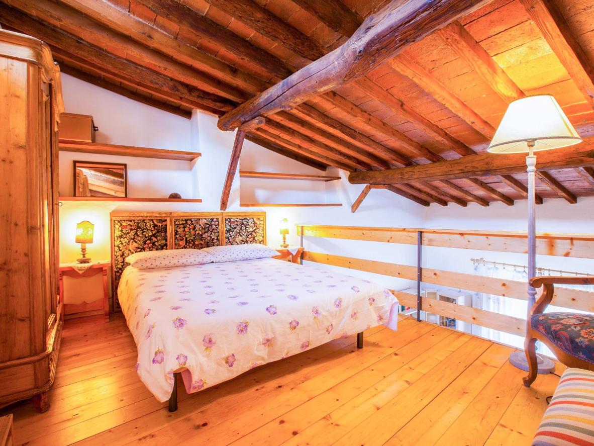 The apartment's loft bedroom has a sloping wooden ceiling