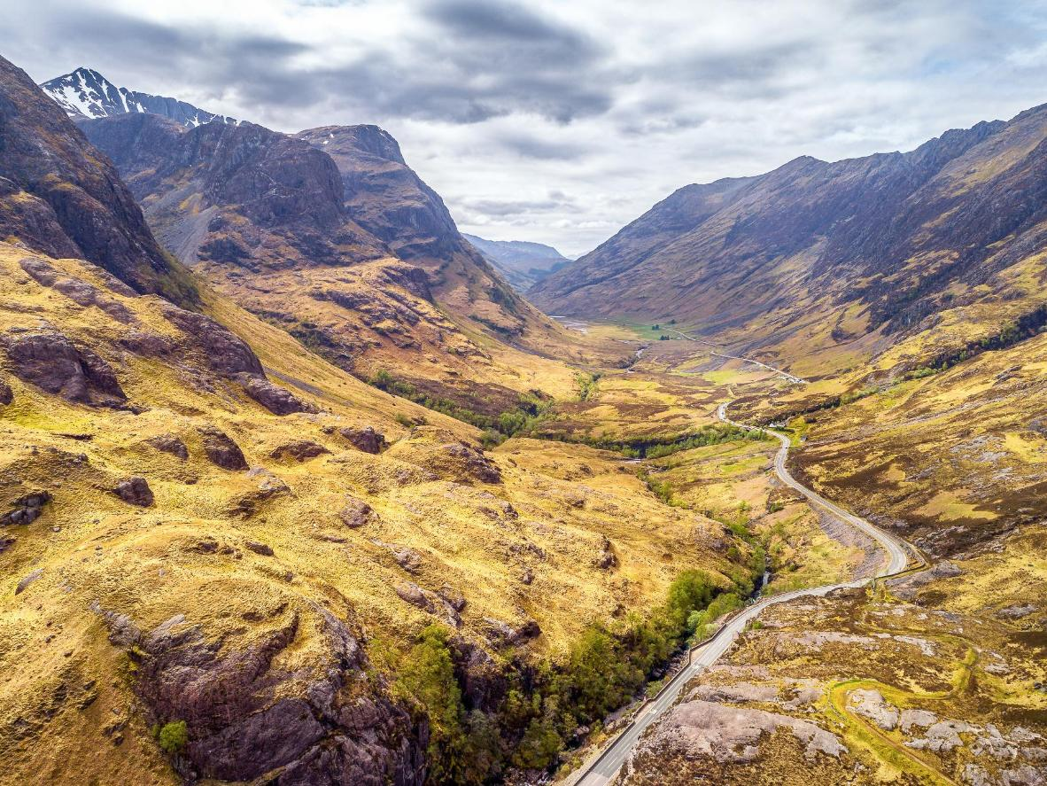 Hike through Glen Coe, a volcanic valley with black and craggy mountains and navy blue lochs