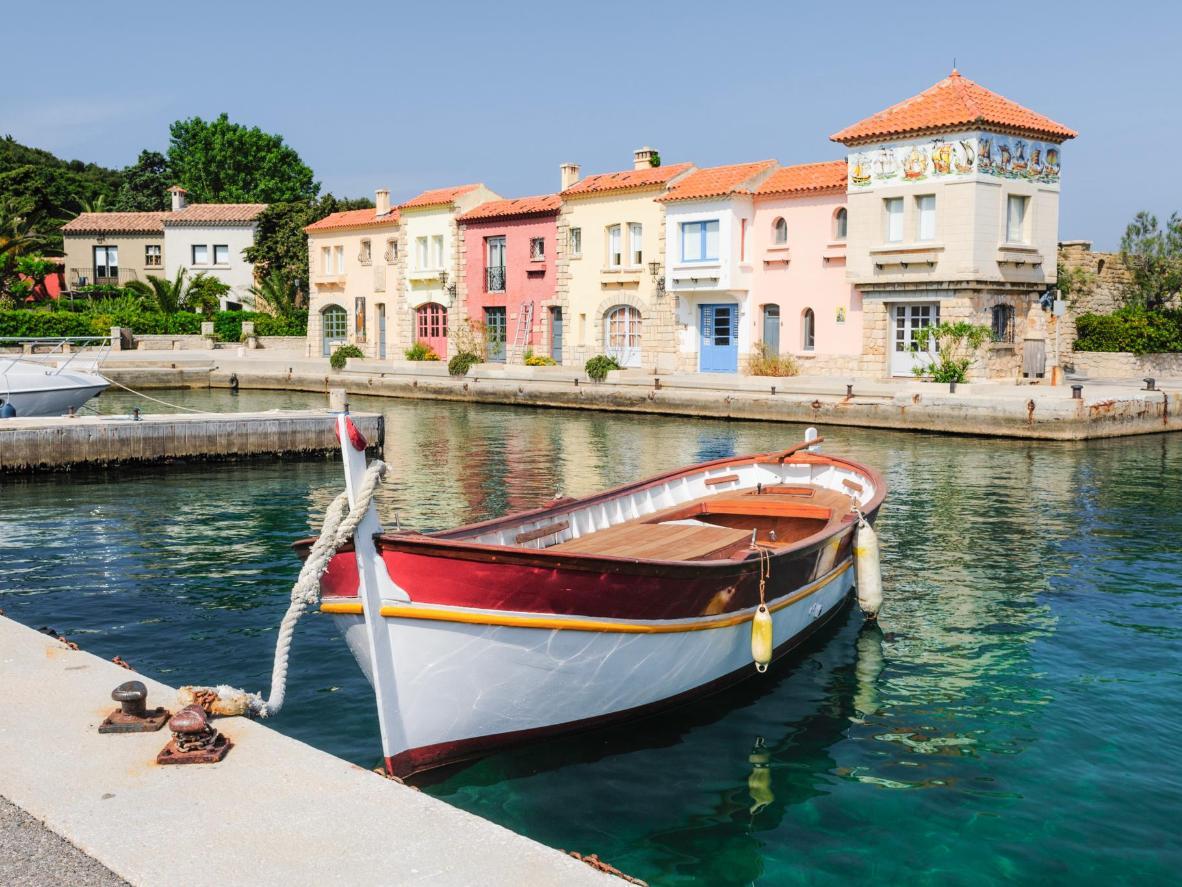 Casas cuadradas, pintadas en colores pastel, bordean la orilla del agua en el pueblo de los artistas en Île de Bendor