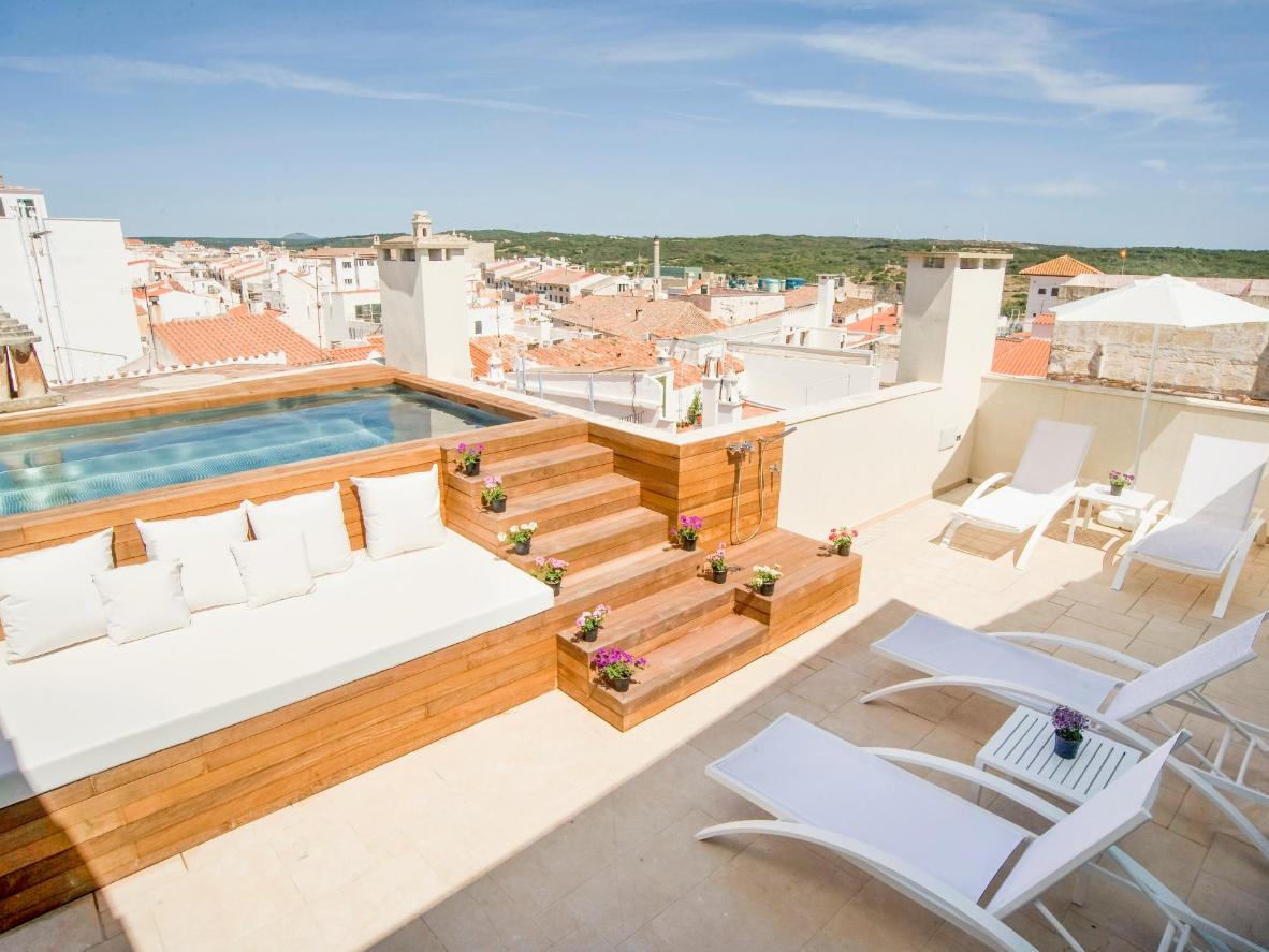 The jacuzzi pool overlooks the terracotta roofs of Mahón