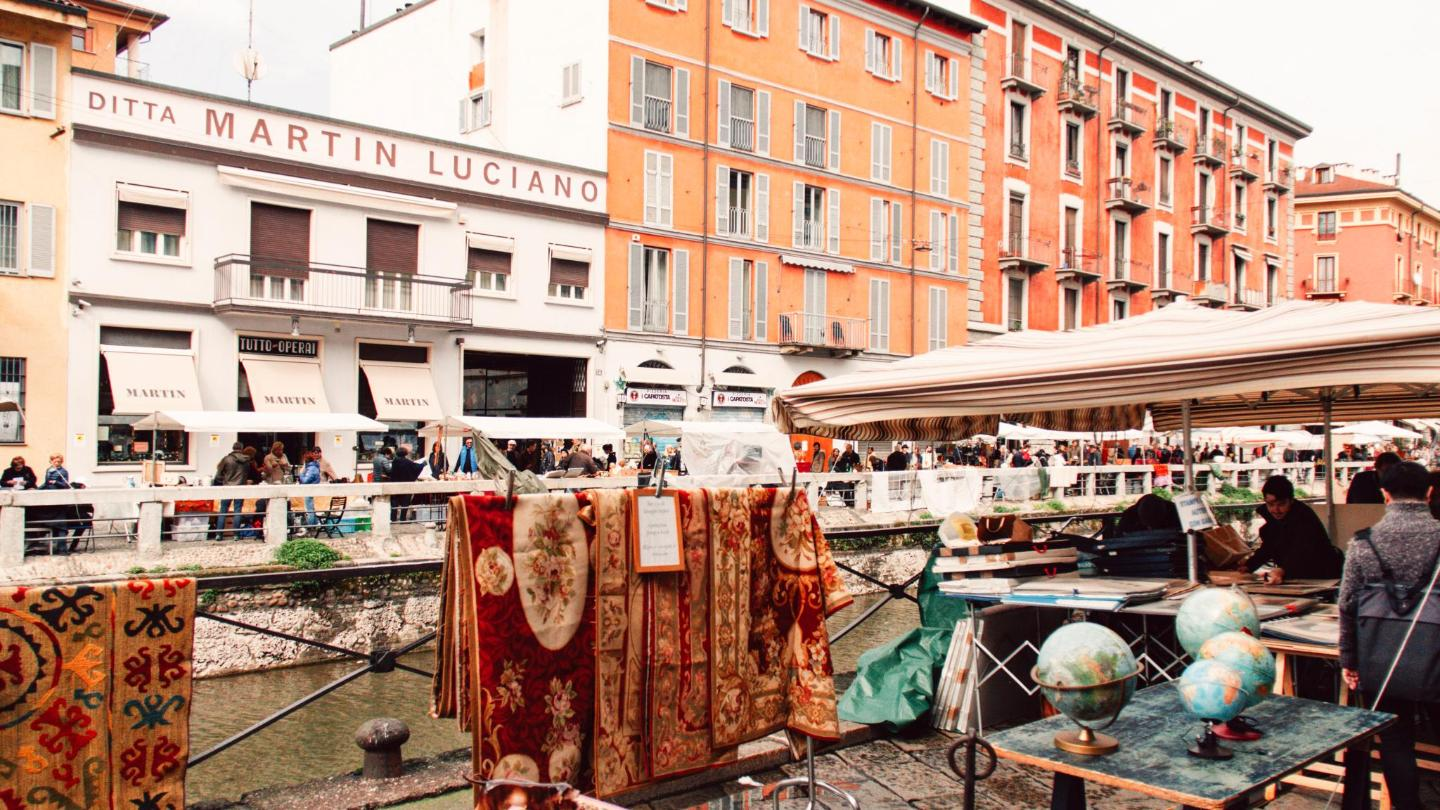 Richly-coloured carpets hang over the canal