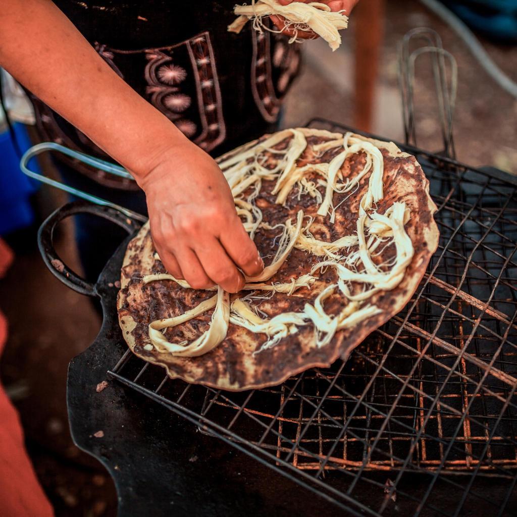 Tlayuda tortilla being prepared at an Oaxaca City market