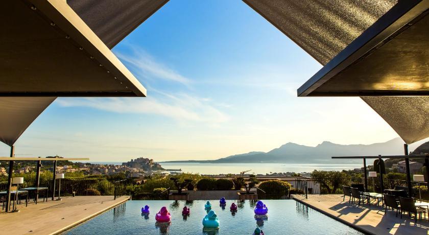 Vue de la piscine et terrasse de l'hôtel donnant sur la mer et la citadelle de Calvi