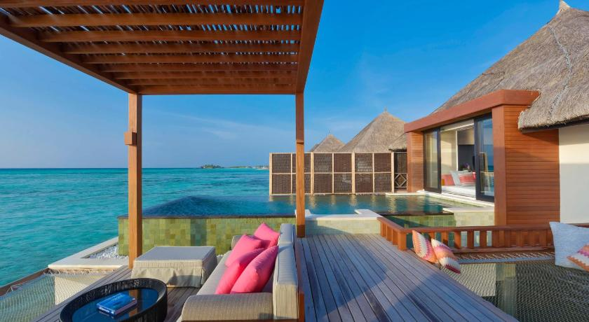Vibrant with tropical flowers, Four Seasons Resort Maldives at Kuda Huraa is a garden-style resort arranged as a traditional Maldivian village on its own coral island.