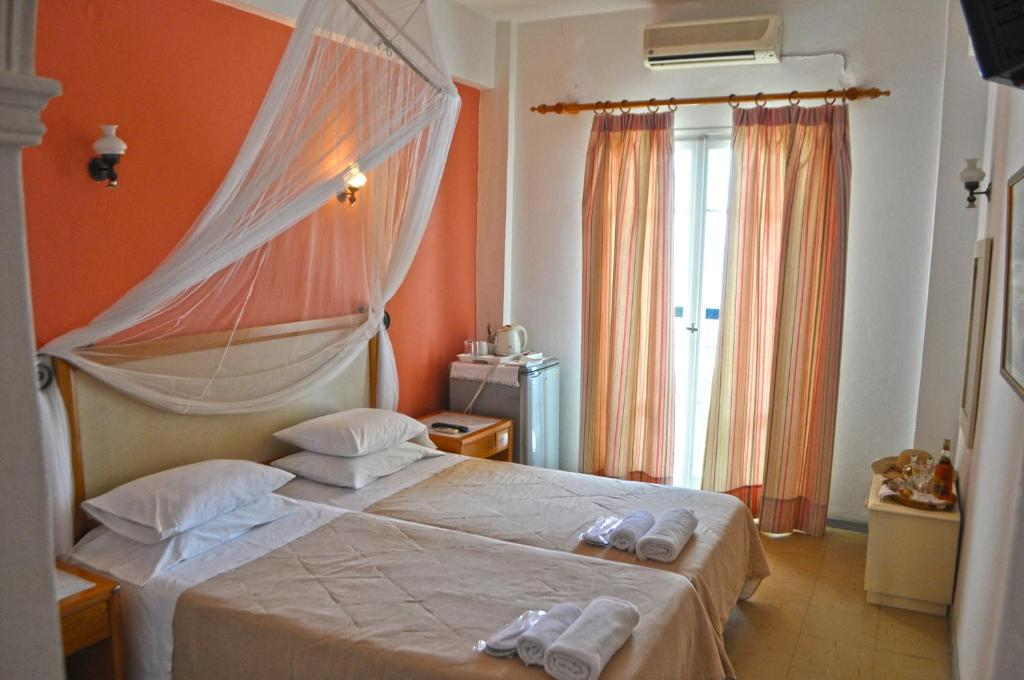 A bed or beds in a room at Eros Beach Hotel