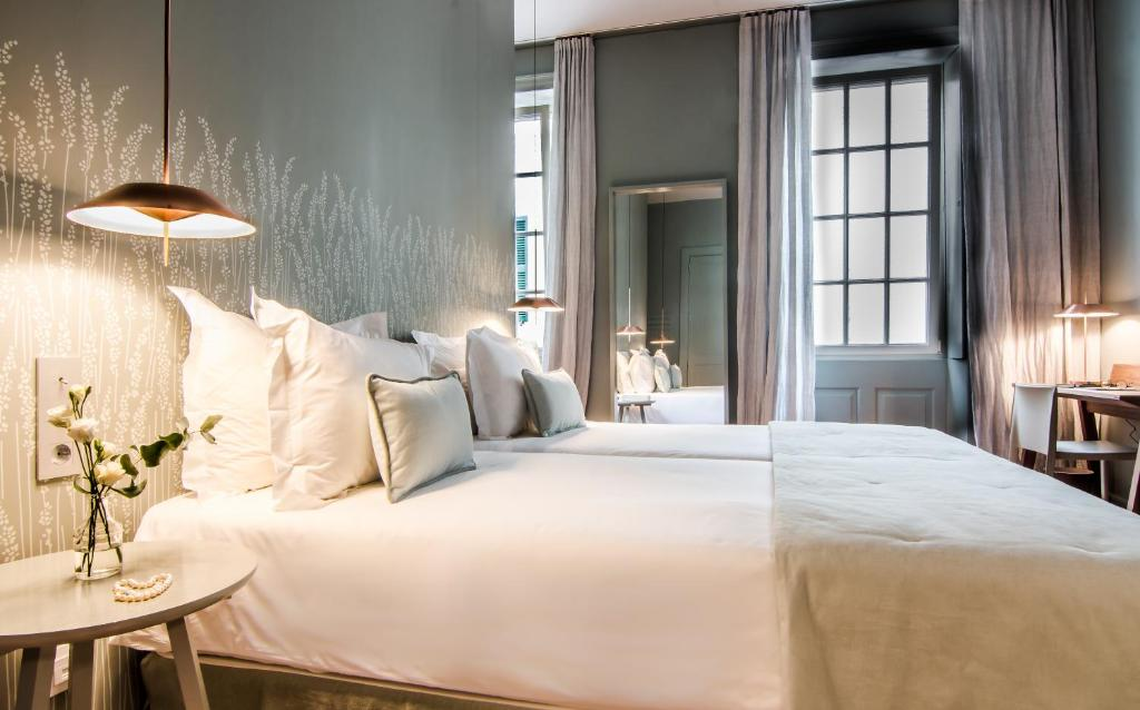 A bed or beds in a room at Casa Ládico - Hotel Boutique
