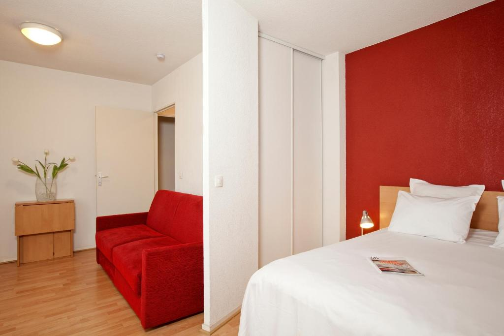 A bed or beds in a room at Séjours & Affaires Paris-Nanterre