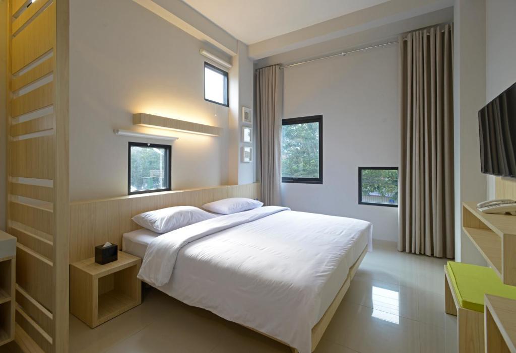 A bed or beds in a room at Arjuna Hotel Batu City