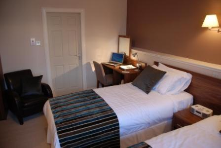 A bed or beds in a room at Kirklands Hotel