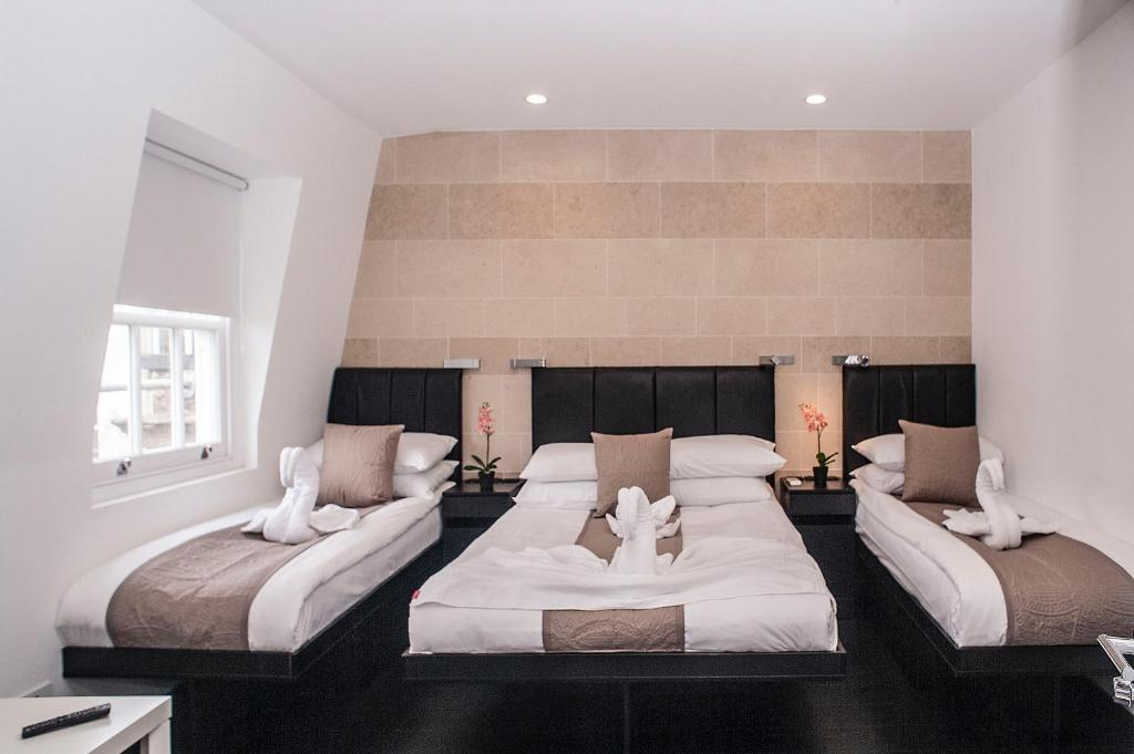 A bed or beds in a room at MStay Hyde Park Hotel