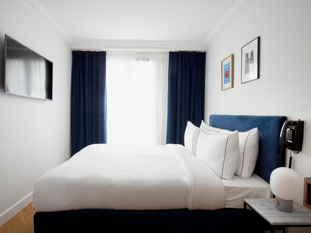 A bed or beds in a room at Hotel Rendez-Vous Batignolles