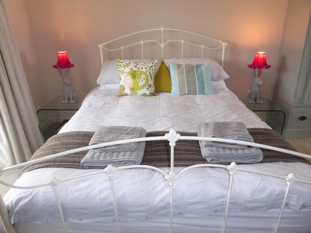 A bed or beds in a room at Rhedyn Guesthouse