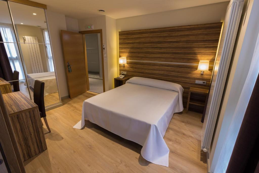 A bed or beds in a room at Hotel Novo Cándido