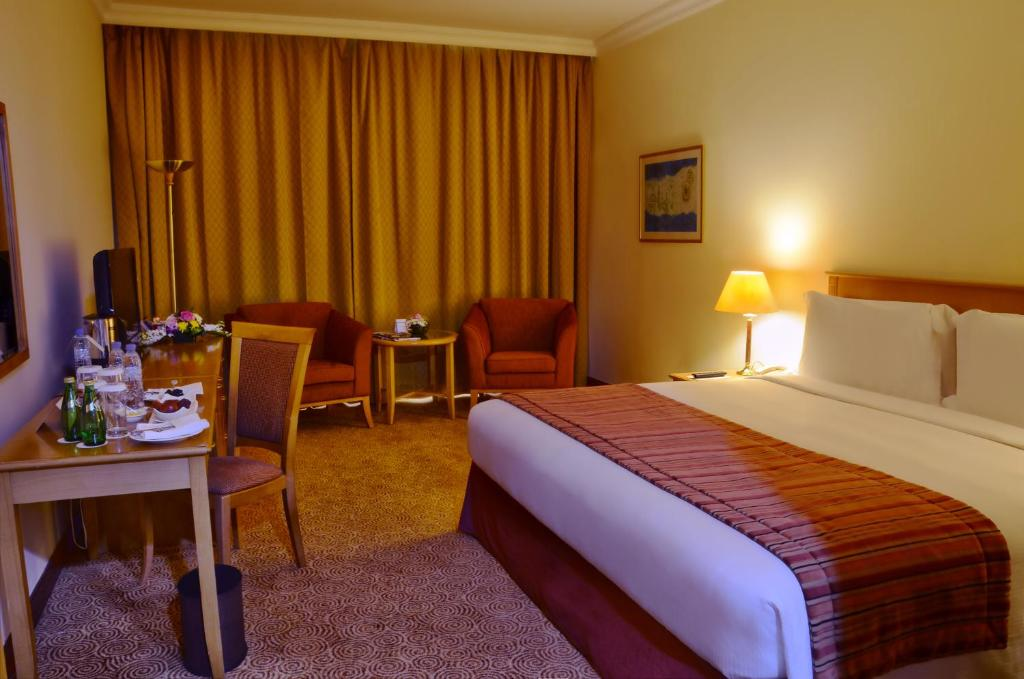 A bed or beds in a room at Swiss-Belhotel Sharjah