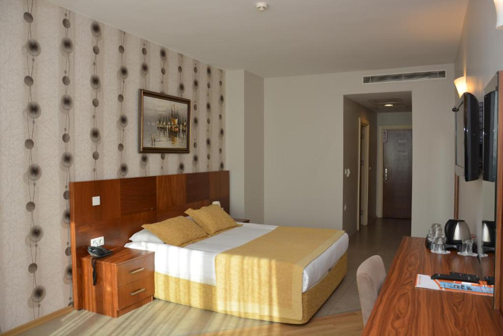 A bed or beds in a room at Grand Karot Hotel