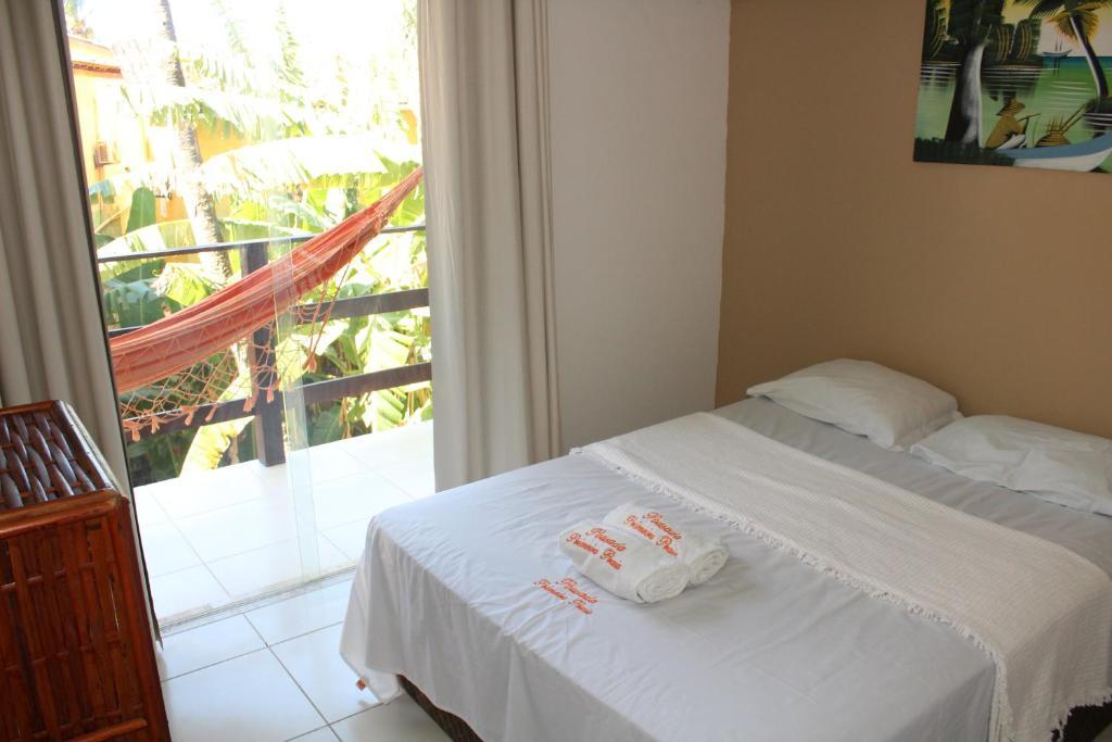 A bed or beds in a room at Pousada Primeira Praia