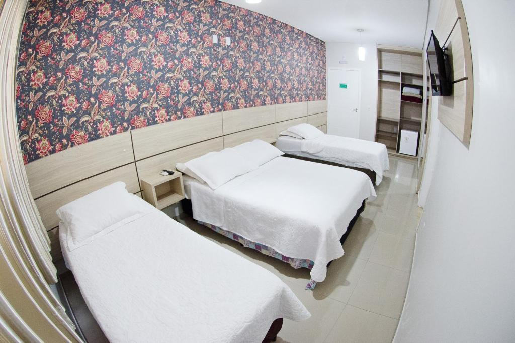 A bed or beds in a room at Hotel Natal