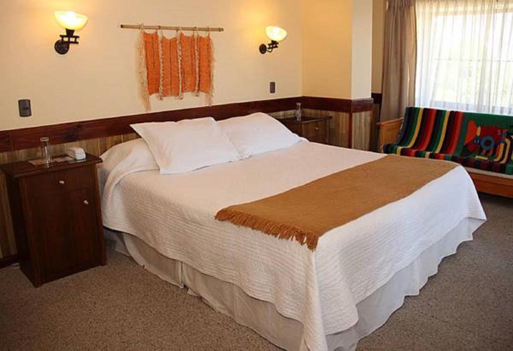 A bed or beds in a room at Hotel Encanto del Río