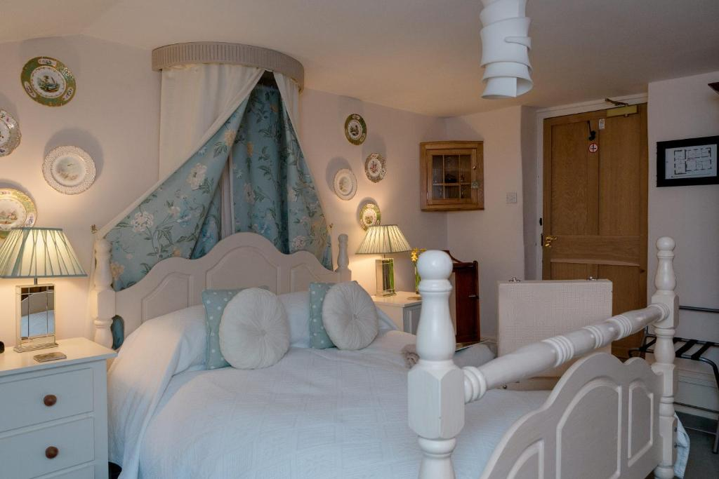 A bed or beds in a room at Muddifords Court Country House