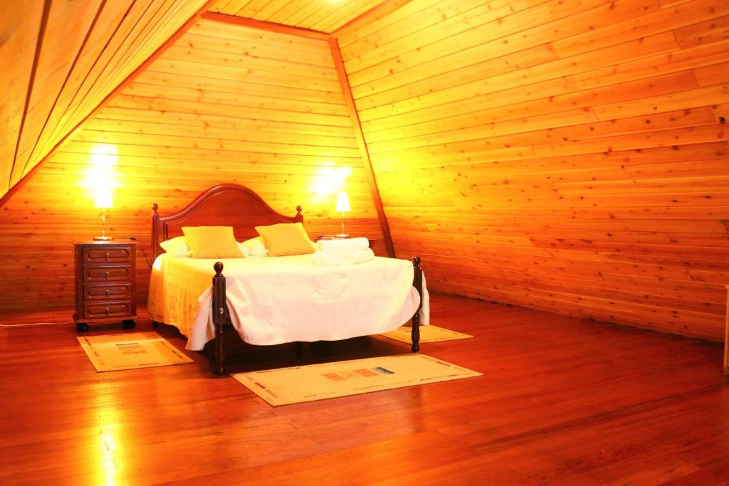A bed or beds in a room at Santo da Serra Country House