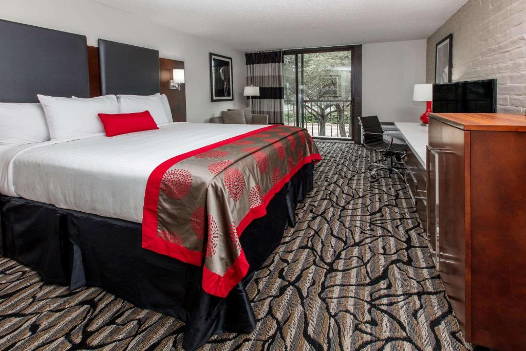 A bed or beds in a room at Ramada by Wyndham Austin South