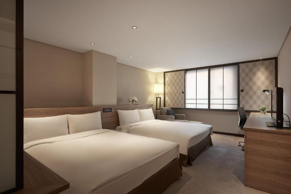 A bed or beds in a room at Royal Inn Taipei Nanxi - MRT Zhongshan Station