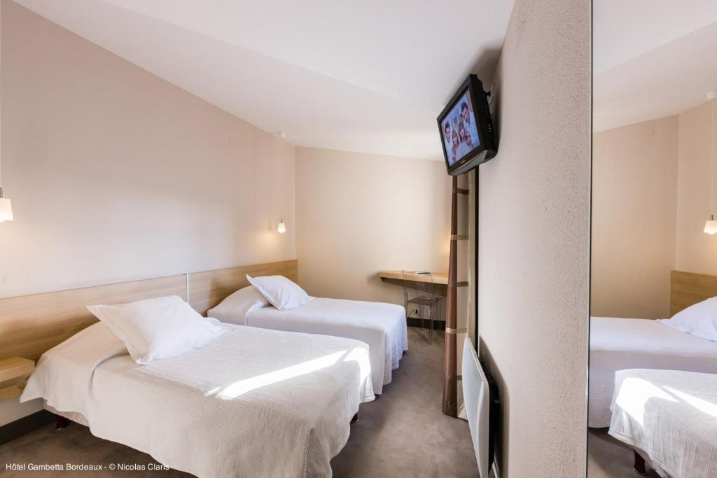 A bed or beds in a room at Hotel Gambetta
