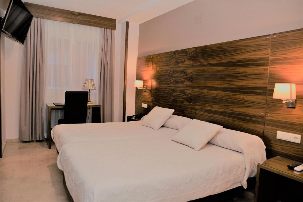 Llit o llits en una habitació de Hotel Escudero