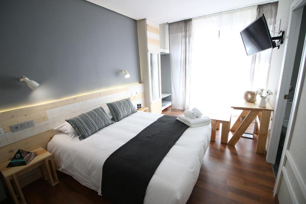 A bed or beds in a room at Hotel Alda Centro Ponferrada