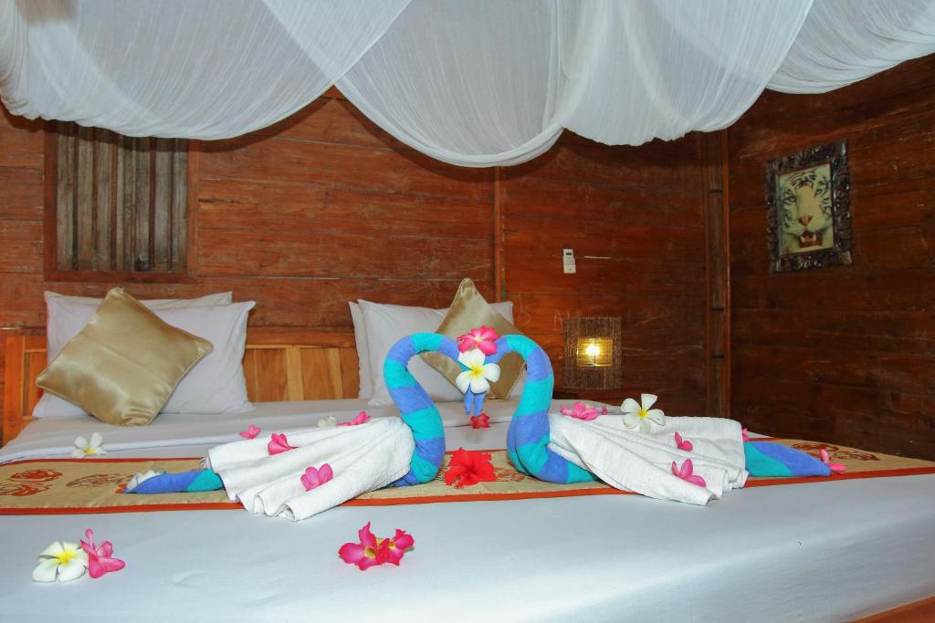 A bed or beds in a room at Unzipp Bungalows Gili Air