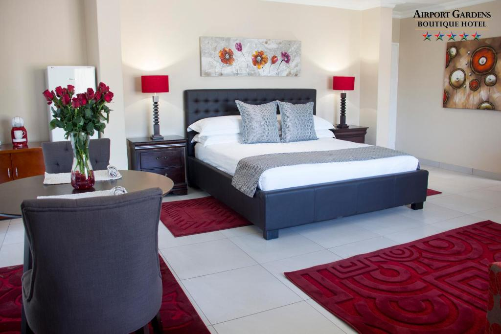 A bed or beds in a room at Airport Gardens Boutique Hotel