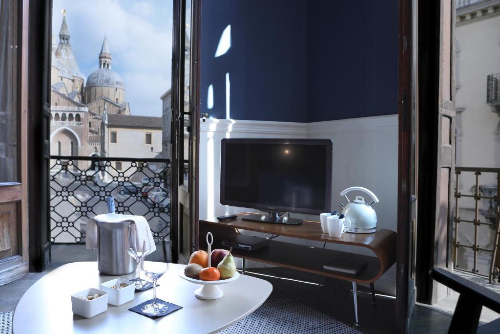 Televízia a/alebo spoločenská miestnosť v ubytovaní Hotel Belludi 37
