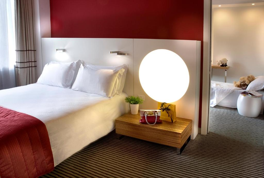A bed or beds in a room at Hotel Rome Pisana