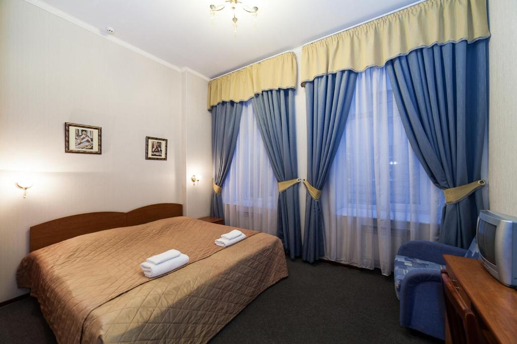 A bed or beds in a room at Amulet Hotel