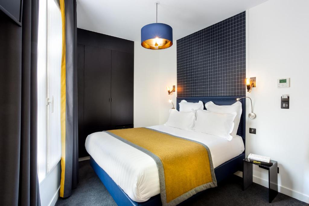 A bed or beds in a room at Hôtel Clarisse