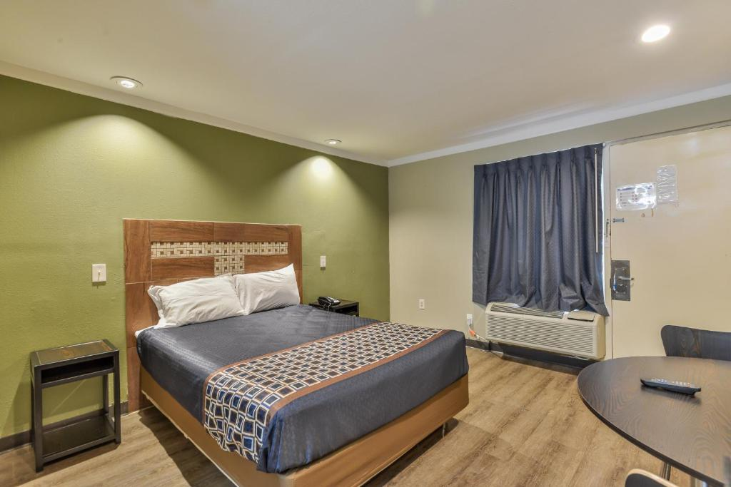 A bed or beds in a room at Budgetel Inn and Suites